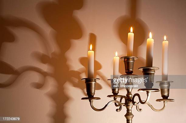Lit candelabra with shadows on wall