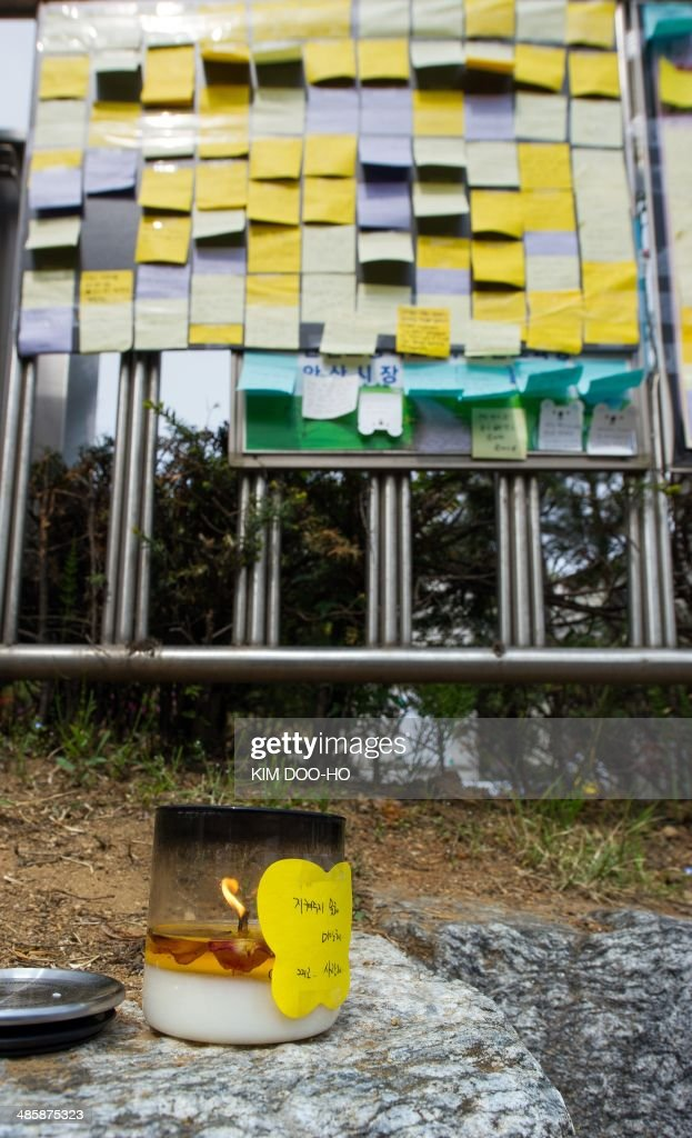 A lit candle burns in front of posted messages of hope (in background) for missing schoolchildren at a makeshift memorial at the main gate of Danwon high school in Ansan on April 21, 2014 where many of the students missing from the sunken South Korean ferry 'Sewol' attended. The captain and crew of the South Korean ferry that capsized last week with hundreds of children on board acted in a way 'tantamount to murder,' President Park Guen-Hye said on April 21, as four more crew members were arrested. AFP PHOTO / KIM DOO-HO