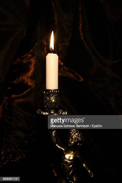 Lit Candle On Figurine Stand