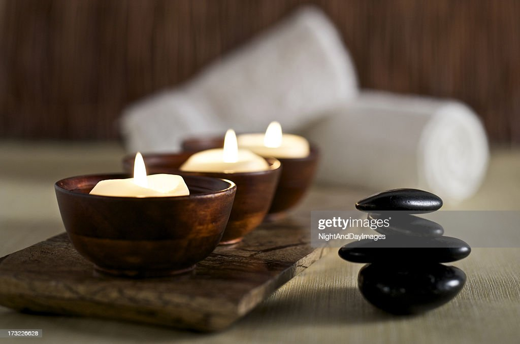 Lit candles and black massage stones in Zen spa : Stock Photo