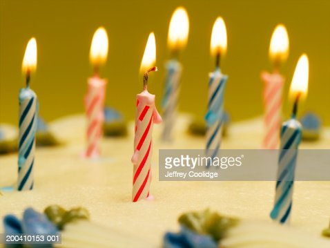 Lit candles and blue decorative flowers on birthday cake, close-up : Stock Photo