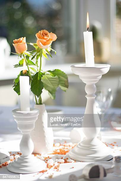 Lit Candles And Flower Vase On Table