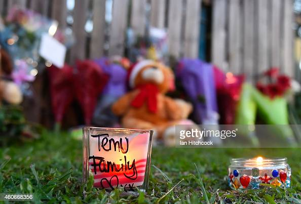 Lit candles are seen resting across the road from the scene of a multiple stabbing in the suburb of Manoora on December 19 2014 in Cairns Australia...