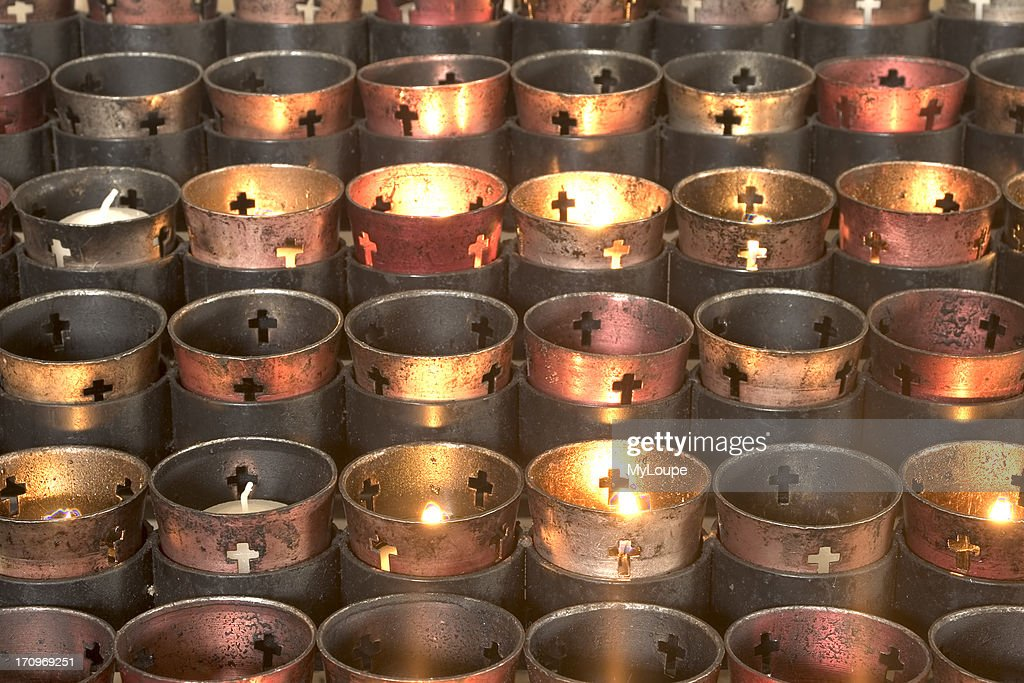 Lit candles at Catholic church, different colors and decorations in a row.