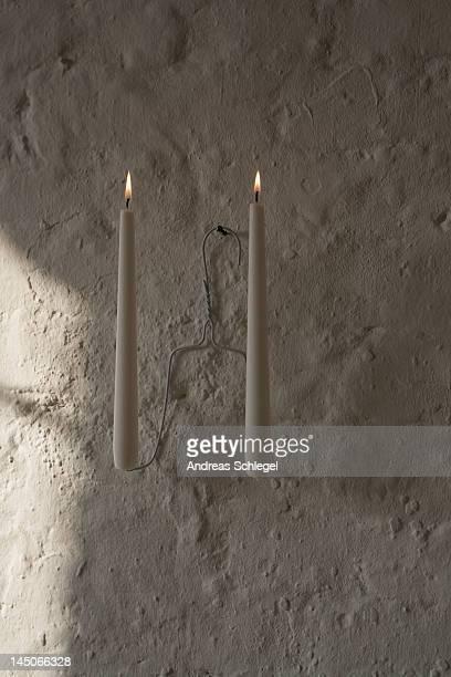 Lit candles on a coat hanger