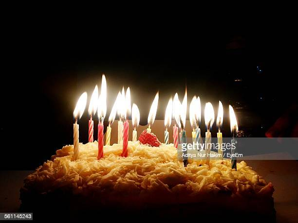 Lit Candles On Birthday Cake In Darkroom