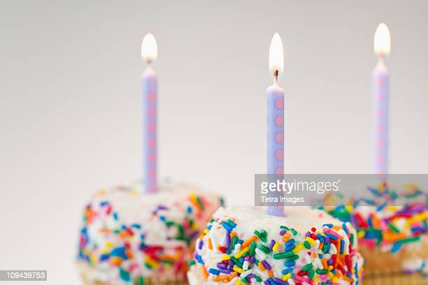 Lit candles on decorated cakes
