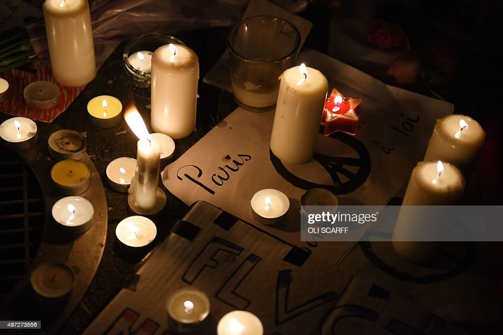 Lit candles sit ontop of signs combining a peace symbol with the Eiffel tower during vigil in Piccadilly Gardens in Manchester, north west England on November 15, 2015, for the victims of the November 13 attacks in Paris. Islamic State jihadists claimed a series of coordinated attacks by gunmen and suicide bombers in Paris on November 13 that killed at least 128 people in scenes of carnage at a concert hall, restaurants and the national stadium.