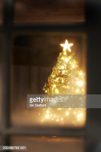 Lit Christmas tree through frosted window : Stock Photo