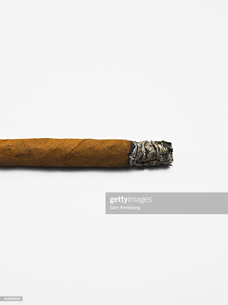 A lit cigar on a white background.