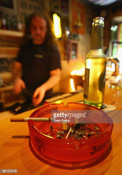 A lit cigarette lies in an ashtray at the Doors Music Pub on the day Germany's highest court partially overturned a smoking ban for pubs on July 30...