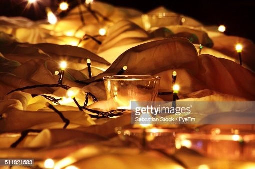 Lit fairy lights and tealight candle on fabric