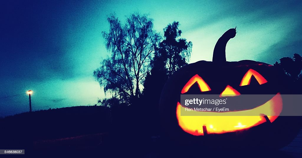 Lit Jack O Lantern On Silhouette Field Against Sky At Dusk During Halloween