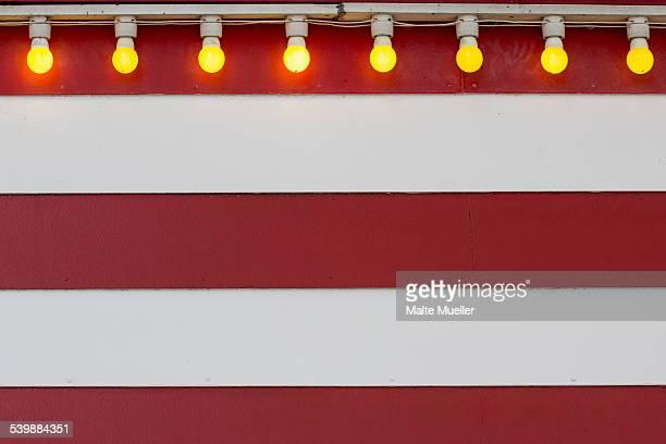 Lit light bulbs on striped wall