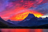 The sky catching fire with the light of the just set sun as the reflection of Mount Grinnell shimmers off Swiftcurrent Lake in Montana's Glacier National Park.
