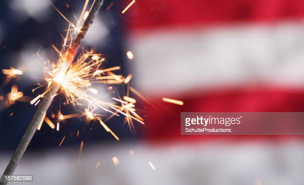 Lit sparkler against a blurred American flag