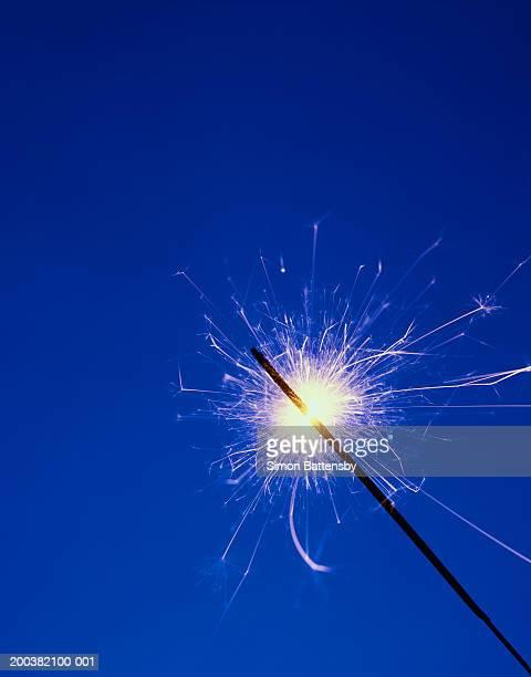 Lit sparkler against blue background, close-up