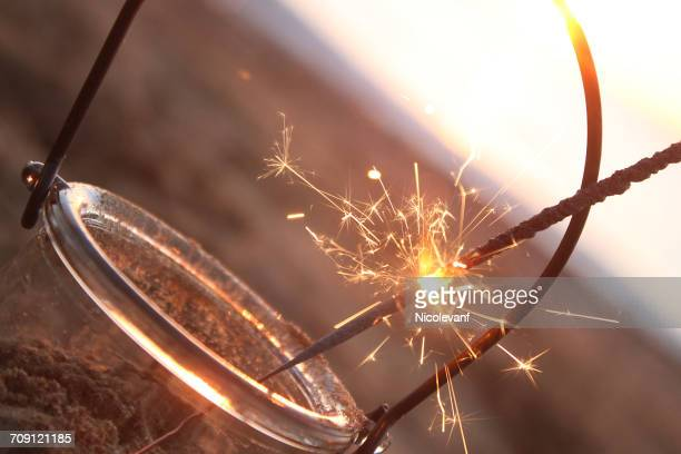 Lit sparkler in a jar on  the beach