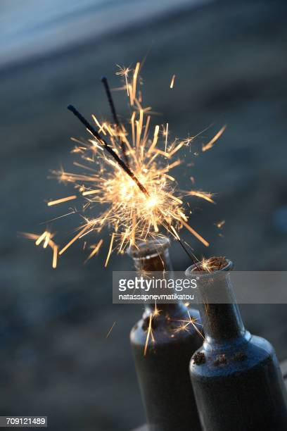Lit sparklers in glass bottles on beach