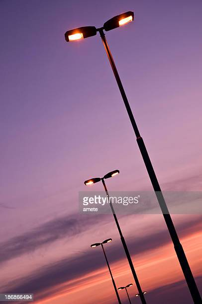 Lit street lamps on sunset background