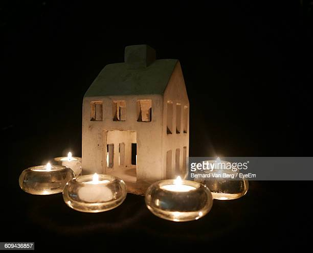 Lit Tea Light Candles Surrounded By Lantern Against Black Background
