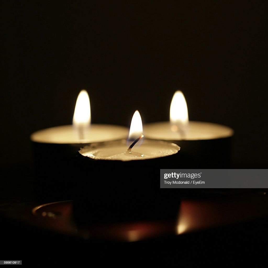 Dark room with candle light - Lit Tealight Candles In Dark Room