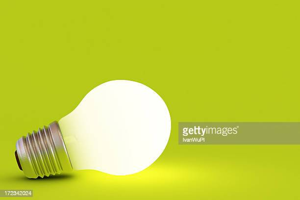 A lit up light bulb on a green background