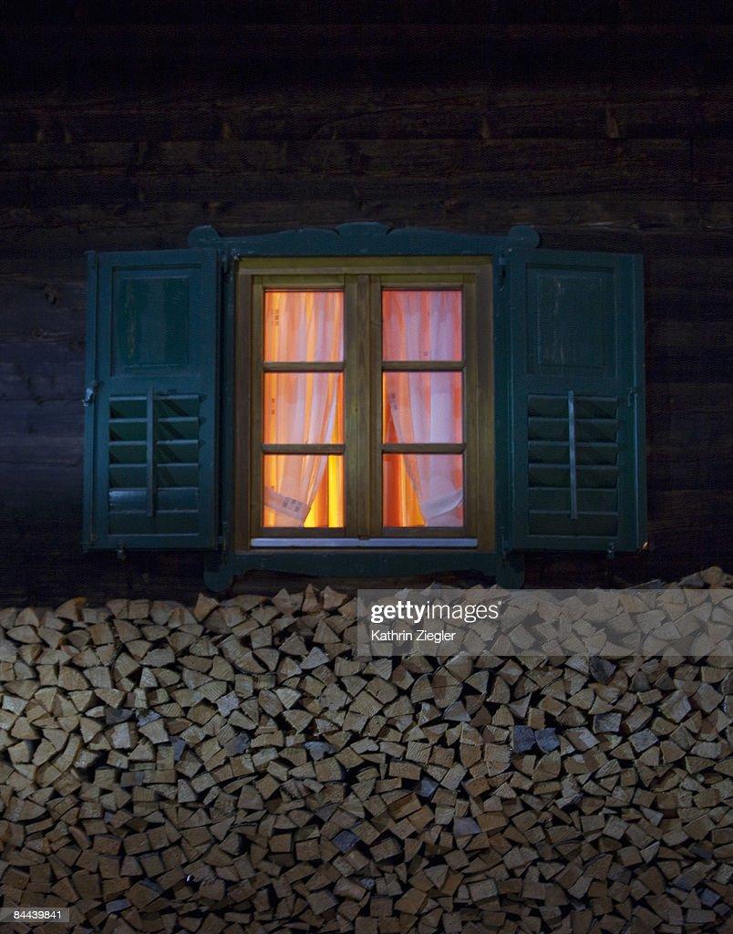 lit window of Alpine hut at night : Stock Photo