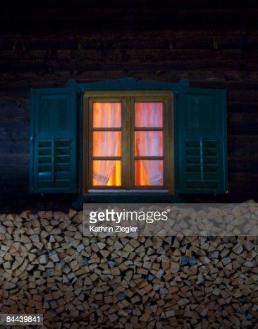 lit window of Alpine hut at night : Foto de stock