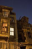 Lit windows of old wooden buildings
