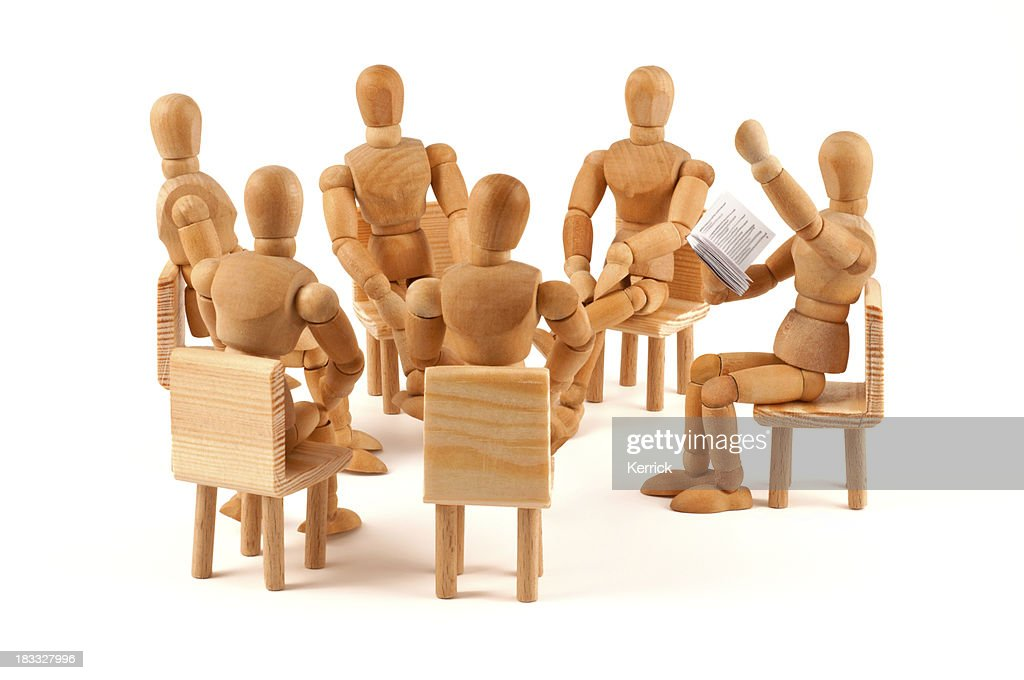 Literarily reading - circle of wooden mannequins listen