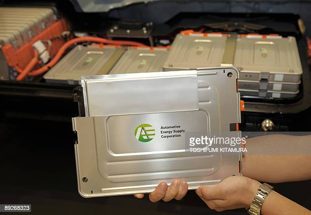 A lithiumion battery cell is displayed in front of the cutmodel of the prototype of Nissan Motors second generation electronic vehicle at its Oppama...
