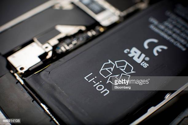 A lithiumion battery sits inside a smartphone sold as an Apple Inc iPhone 4S in an arranged photograph in Hong Kong China on Saturday Jan 11 2014...