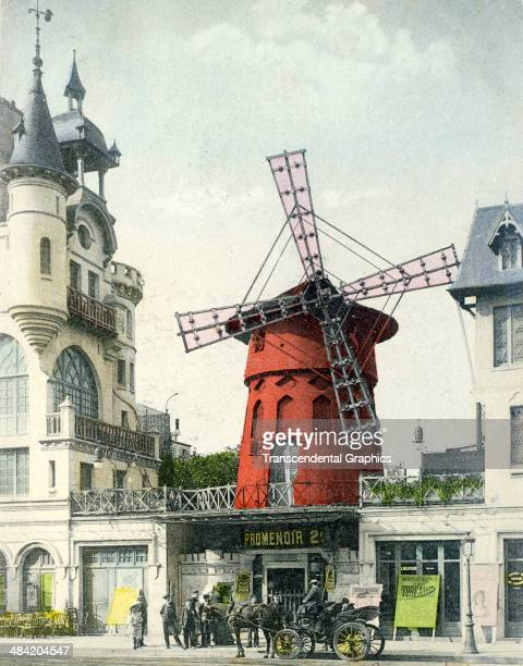 A lithographic postcard from a photo featuring the famous theatrical venue the Moulin Rouge is produced in Paris France around 1910 A group of people...