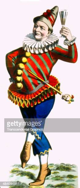 A lithographic poster for a French carnival sideshow featuring a clown or jester doing a jig is produced in Paris France around 1900 He carries a...