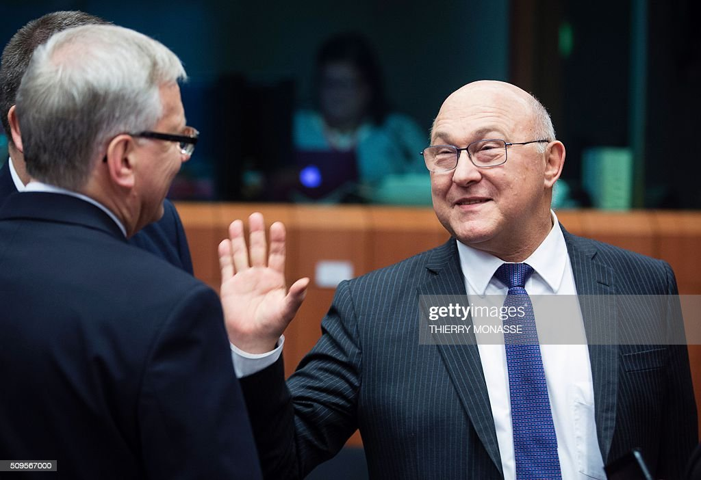 Lithuanian Finance Minister Rimantas Sadzius (L) talks to French Finance and Public Accounts Minister Michel Sapin (R) prior to a meeting of Eurogroup ministers at the European Council headquarters in Brussels on February 11, 2016. / AFP / THIERRY MONASSE