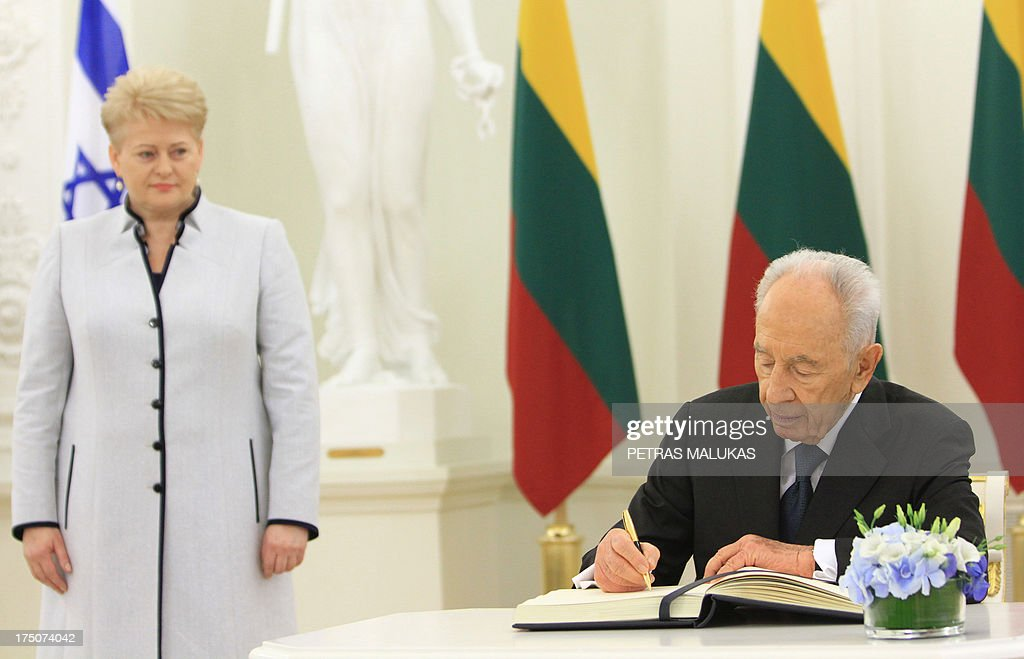 Lithuanian President Dalia Grybauskaite (L) looks on as Israeli President Shimon Peres signs the guest book on July 31, 2013 at the presidential palace in Vilnius, Lithuania.