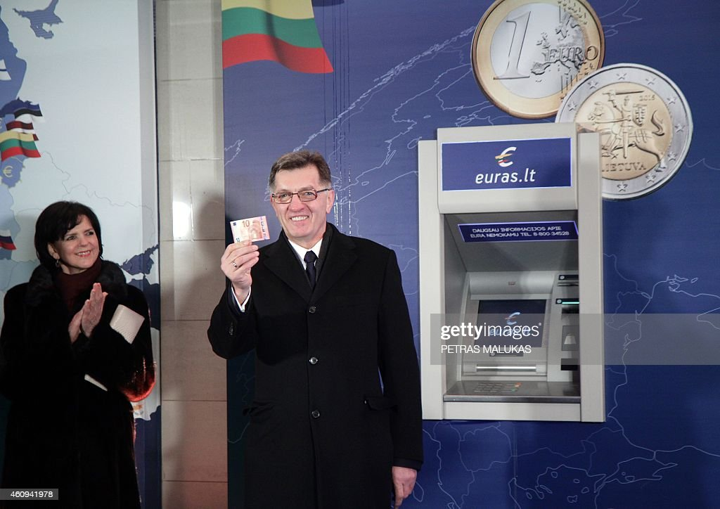 Lithuanian Prime Minister Algirdas Butkevicius withdraws euros from a bank machine on January 1, 2015 during a ceremony in Vilnius. Lithuania switched over to the euro on January 1st, becoming the last Baltic nation to adopt Europe's single currency in a bid to boost stability despite fears of inflation and eurozone debt woes. AFP PHOTO / PETRAS MALUKAS