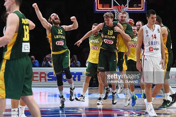 Lithuania's center Antanas Kavaliauskas and Lithuania's forward Mindaugas Kuzminskas celebrate as Serbia's power forward Zoran Erceg looks on after...