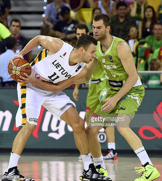 Lithuania's centre Donatas Motiejunas vies with Slovenia's centre Uros Slokar during the 2014 FIBA World basketball championships group D match...