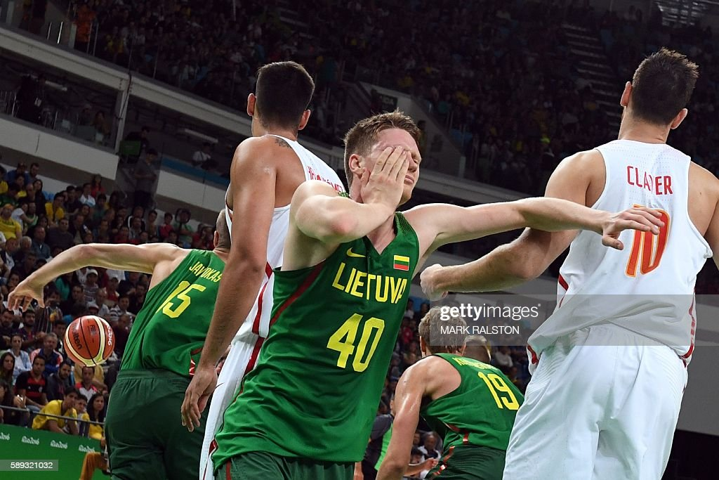 TOPSHOT Lithuania's small forward Marius Grigonis holds his face and falls after being knocked during a Men's round Group B basketball match between...