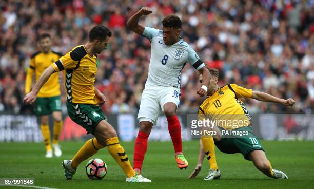 Lithuania's Tadas Kijanskas England's Alex OxladeChamberlain and Lithuania's Arturas Zulpa battle for the ball during the World Cup Qualifying match...