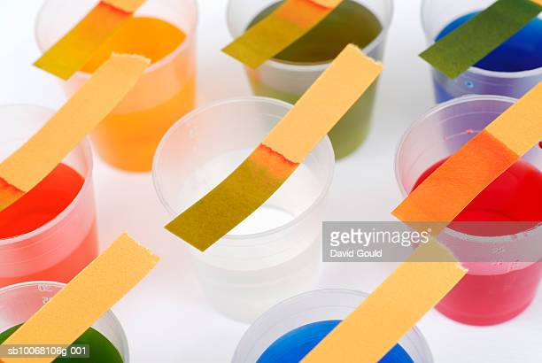 Litmus test strips on top of plastic cups with various multicolored liquids, studio shot