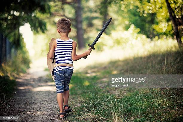 Litte boy playing knight walking on forest path