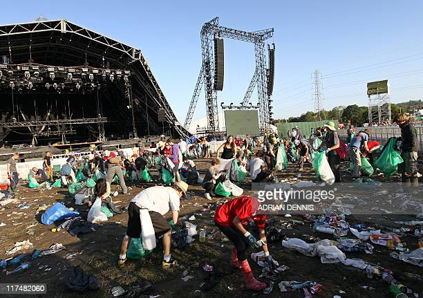 Litter pickers begin collecting the rubbish scattered by The Pyramid Stage following the Glastonbury festival near Glastonbury Somerset on June 27...