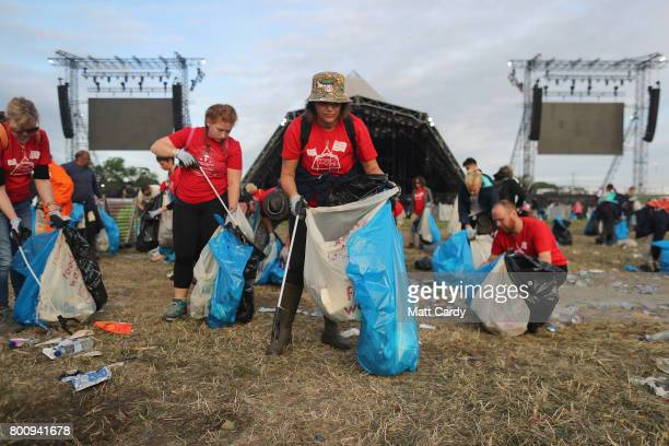 Litter pickers begin the job of clearing the fields at the Glastonbury Festival site at Worthy Farm in Pilton on June 26 2017 near Glastonbury...