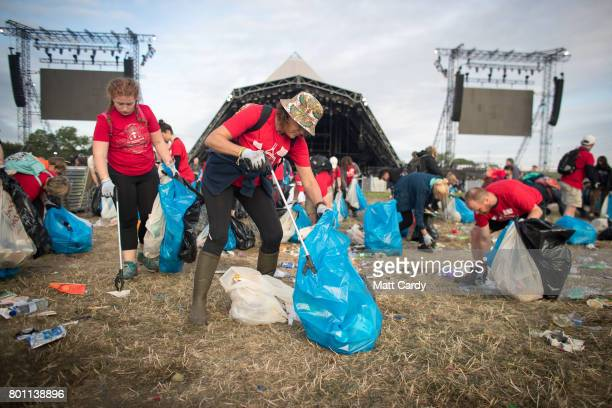 Litter pickers collect rubbish in front of the Pyramid Stage as festival goers leave the Glastonbury Festival site at Worthy Farm in Pilton on June...