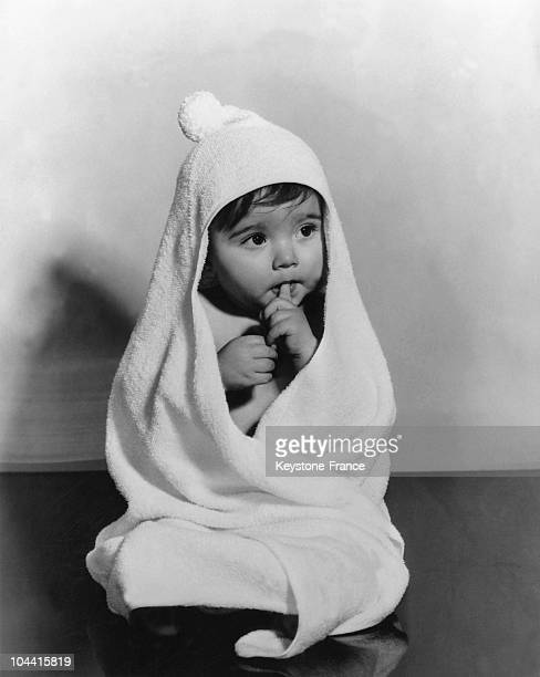 A little 8month old girl in a white terrycloth bathrobe the 'latest style' without seams in France on January 20 1960