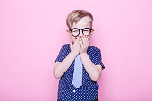 Little adorable kid in tie and glasses. School. Preschool. Fashion. Studio portrait over pink background