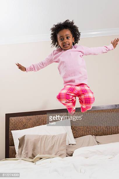 Little African American girl bouncing on bed in mid air
